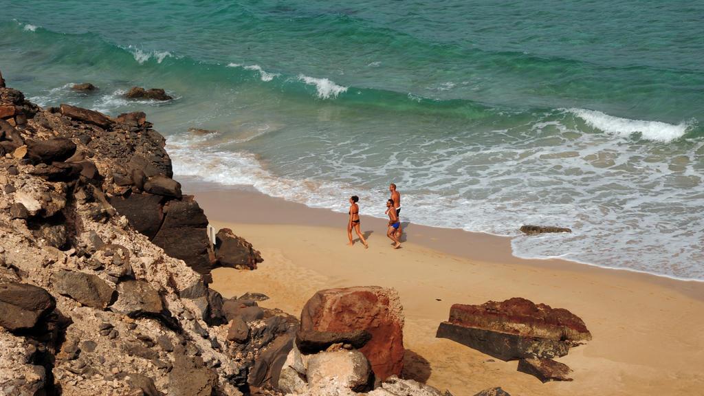 Drei Personen schlendern einen weißen Sandstrand entlang