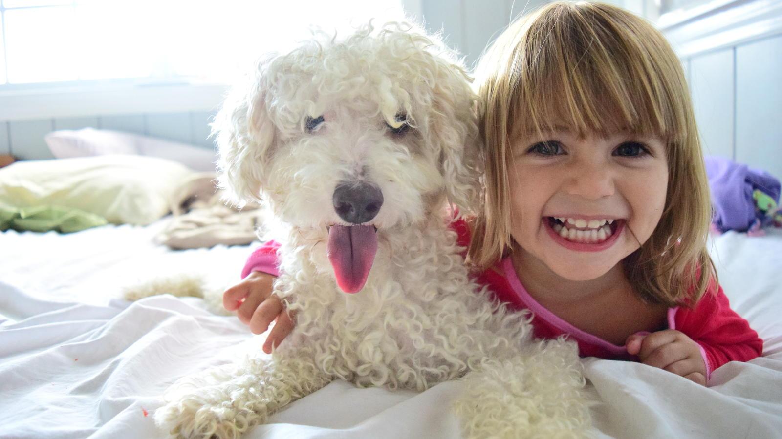 Mädchen kuschelt mit Hund