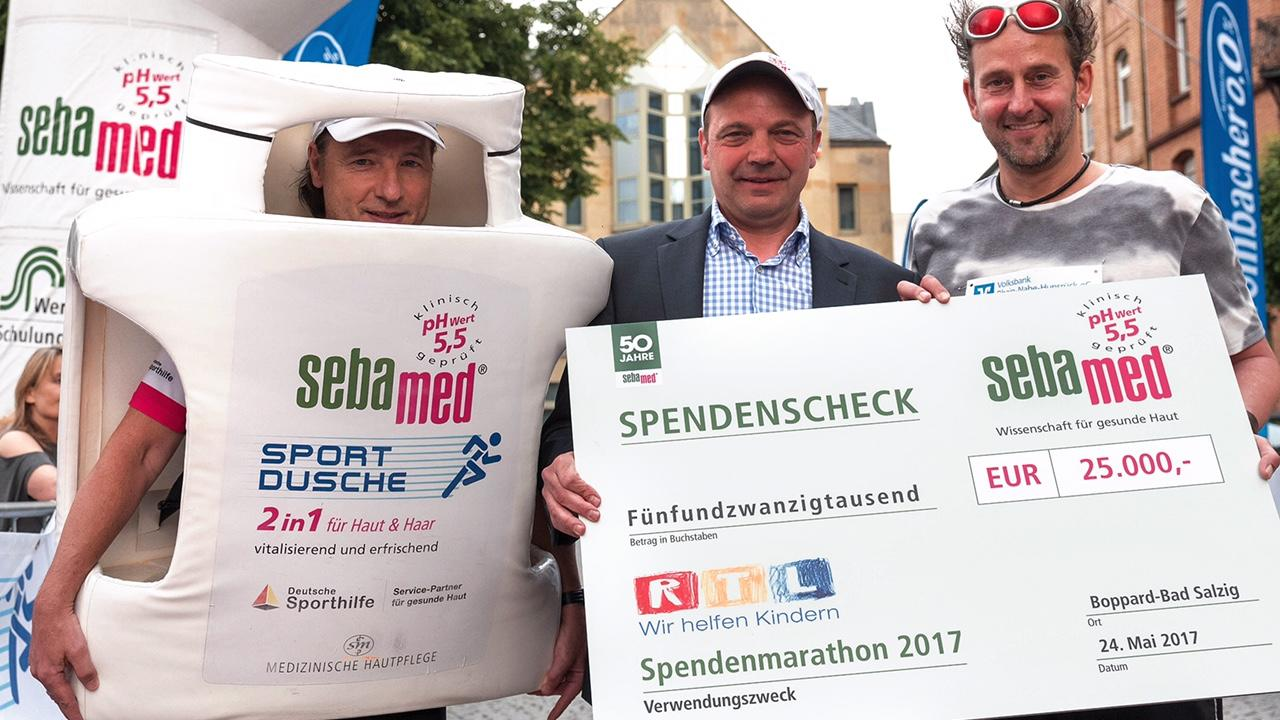 sebamed Sportmarketing Manager Toni Neier überreicht Tom Lehel den sebamed Spendenscheck in Höhe von 25.000 EUR.