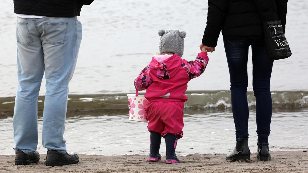 ARCHIV - Eine Familie mit Kleinkind ist am 04.03.2017 am Strand des Ostseebades Warnemünde (Mecklenburg-Vorpommern) unterwegs. Die Babys von heute leben vielleicht noch länger als bisher erwartet. 2017 geborene Jungen könnten durchschnittlich bis zu