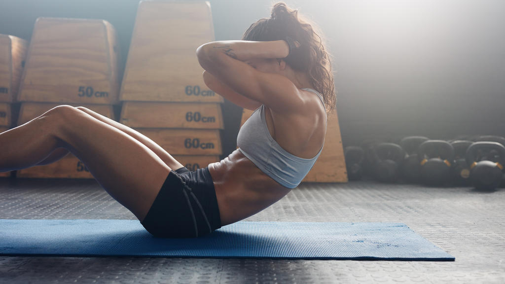 Sporty young female athlete on yoga mat doing situps in gym. Fitness woman doing abs crunches.