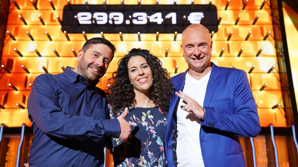 Moderator Frank Buschmann (l.) mit den Kandidaten Sabrina (37) und Basel (40) aus Meckenheim, die sich über ihren Gewinn von 299.341 Euro freuen.