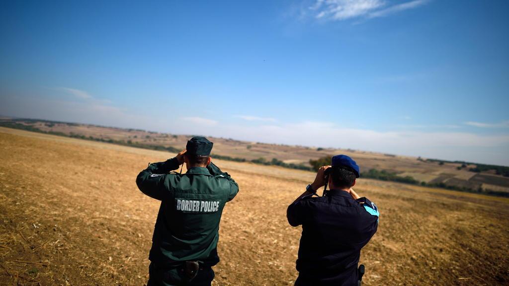 ARCHIV - Zwei Beamte der europäischen Grenzschutzagentur Frontex aus Bulgarien (l) und den Niederlanden beobachten am 07.10.2016 mit Ferngläsern die bulgarisch-türkische Grenze nahe dem Grenzübergang Kapitan Andreevo (Bulgarien). (zu dpa «Bulgarien s