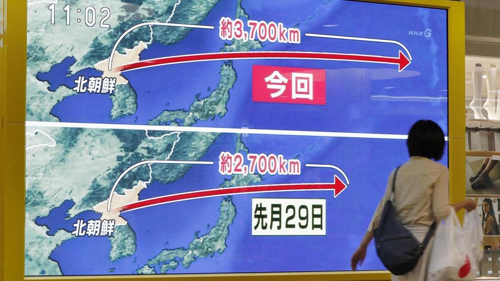 Eine Frau geht am 15.09.2017 in Sapporo (Japan) an einem Monitor vorbei, auf dem der erneute nordkoreanische Raktentest illustriert wird. Zwölf Tage nach seinem weltweit verurteilten Atomtest hat Nordkorea erneut eine Rakete über Japan hinweg in den