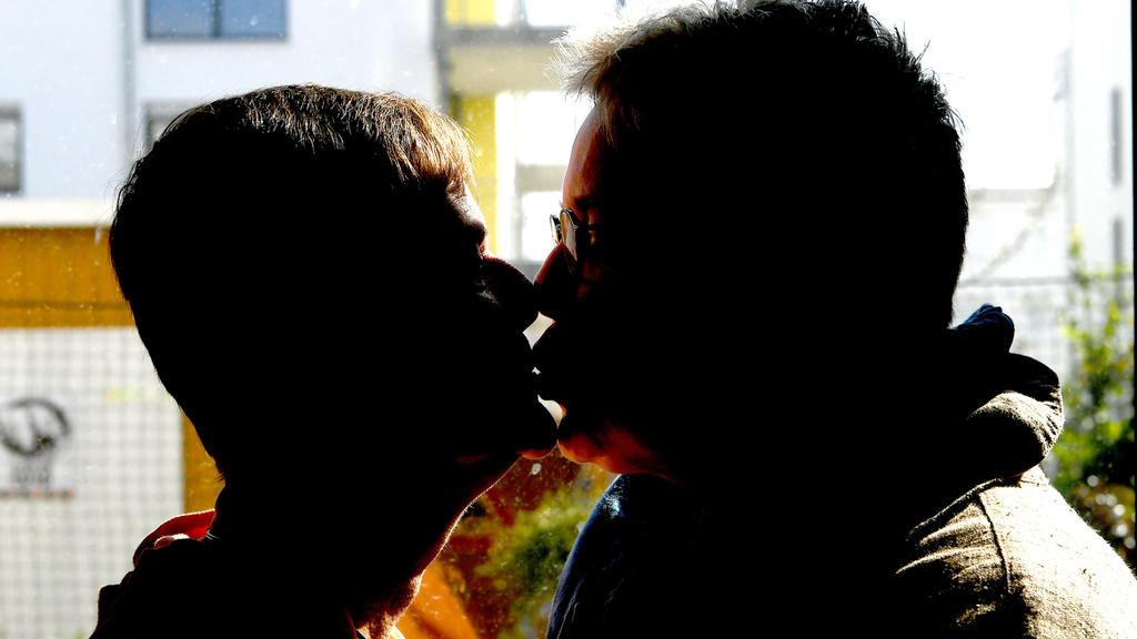 """Das lesbische Ehepaar Claudia und Dorle Göttler (r-l) küsst sich am 13.09.2017 in ihrem Wohnzimmer ihres Hauses in Hemmingen-Arnum (Niedersachsen).     (zu """"Themenpaket Ehe für alle"""" vom 29.09.2017) Foto: Holger Hollemann/dpa +++(c) dpa - Bildfunk+++"""