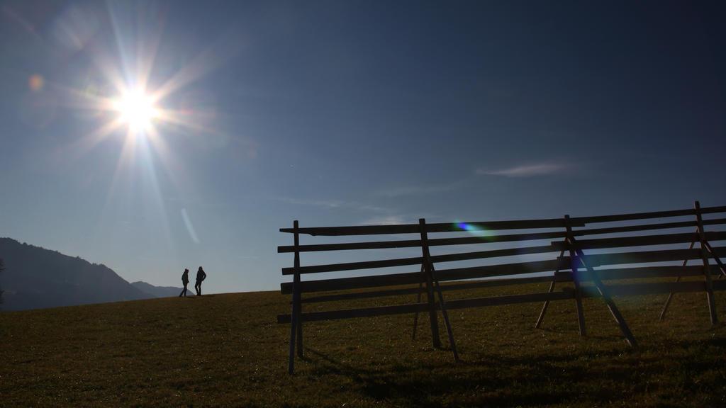 Spaziergänger laufen am Sonntag (13.11.2011) hinter Schneefangzäunen bei Maria Rain (Schwaben) im Sonnenschein. Sonnig und für die Jahreszeit ungewöhnlich mild ist das Wetter am bayerischen Alpenrand. Foto: Karl-Josef Hildenbrand dpa/lby | Verwendung