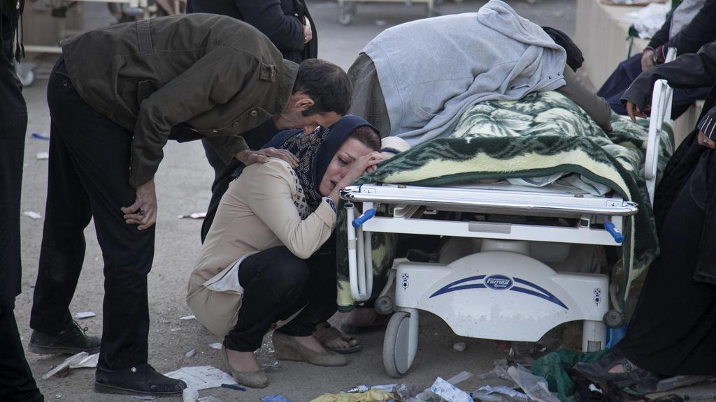 HANDOUT - Dieses von der Tasnim News Agency zur Verfügung gestellte Foto zeigt am 13.11.2017 in Sarpol-E-Zahab (Iran) Familienangehörige, die vor der Leiche eines Opfers des Erdbebens trauern. Nach dem schweren Erdbeben in den südlichen Kurdengebiete