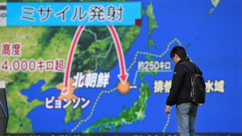 Ein Mann steht am 29.11.2017 in Tokio, Japan, vor einem riesigen Bildschirm, der eine Nachrichtensendung zu einem Raketenstart Nordkoreas zeigt. Nordkorea hat seine bisher weitreichendste Interkontinentalrakete getestet, die möglicherweise bis in die