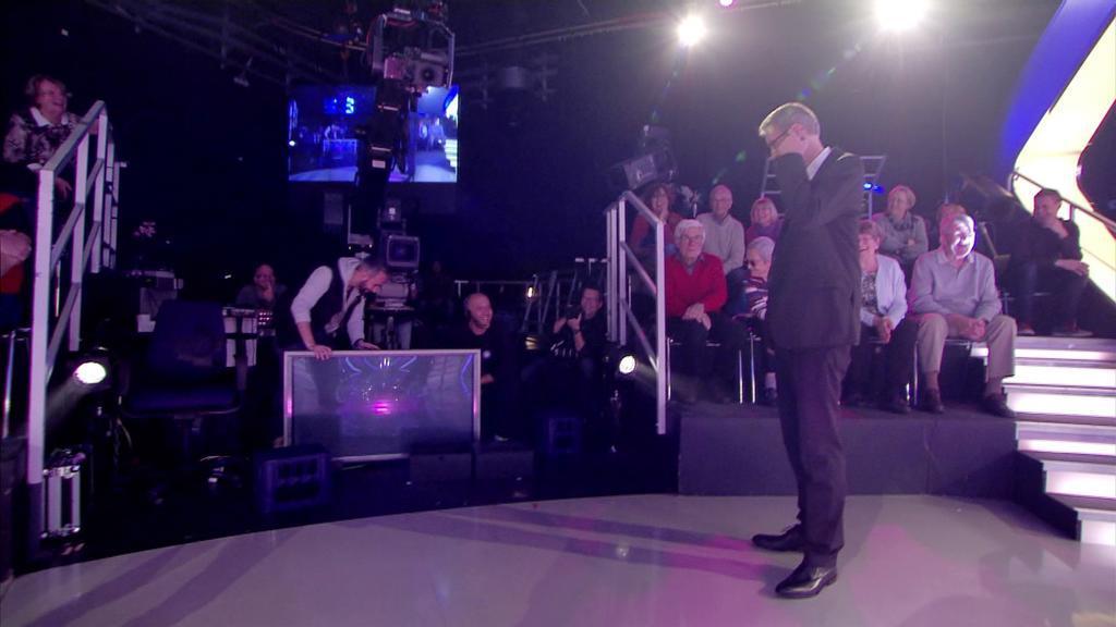 Ein Fernseher ist während der Sendung umgekippt. Günther Jauch schaut sich das aus der Nähe an.