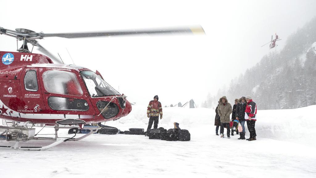Touristen stehen mit ihrem Gepäck am 21.01.2018 auf dem Dach des Matterhorn Terminals in Täsch (Schweiz) um per Hubschrauber zum Wintersportort Zermatt zu fliegen. Zermatt in der Schweiz ist nach ergiebigen Schneefällen erneut weitgehend von der Auße