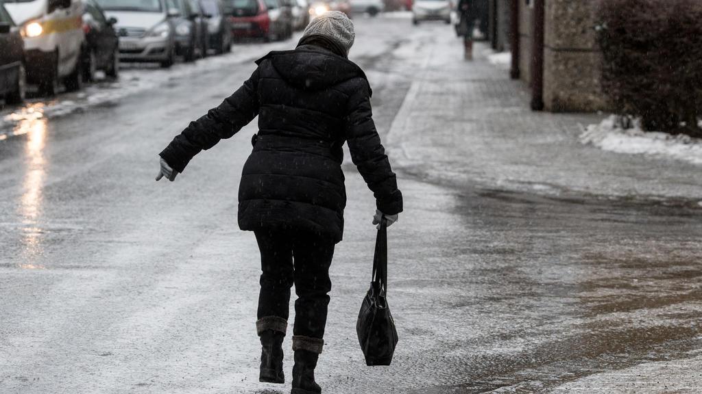 Eine Frau geht am 31.01.2017 in Straubing (Bayern) vorsichtig auf einer vereisten Straße. Der Deutsche Wetterdienst (DWD) warnt vor Glatteis in vielen bayerischen Landkreisen. Vor allem in der Oberpfalz, in Niederbayern und im bayerischen Wald müssen