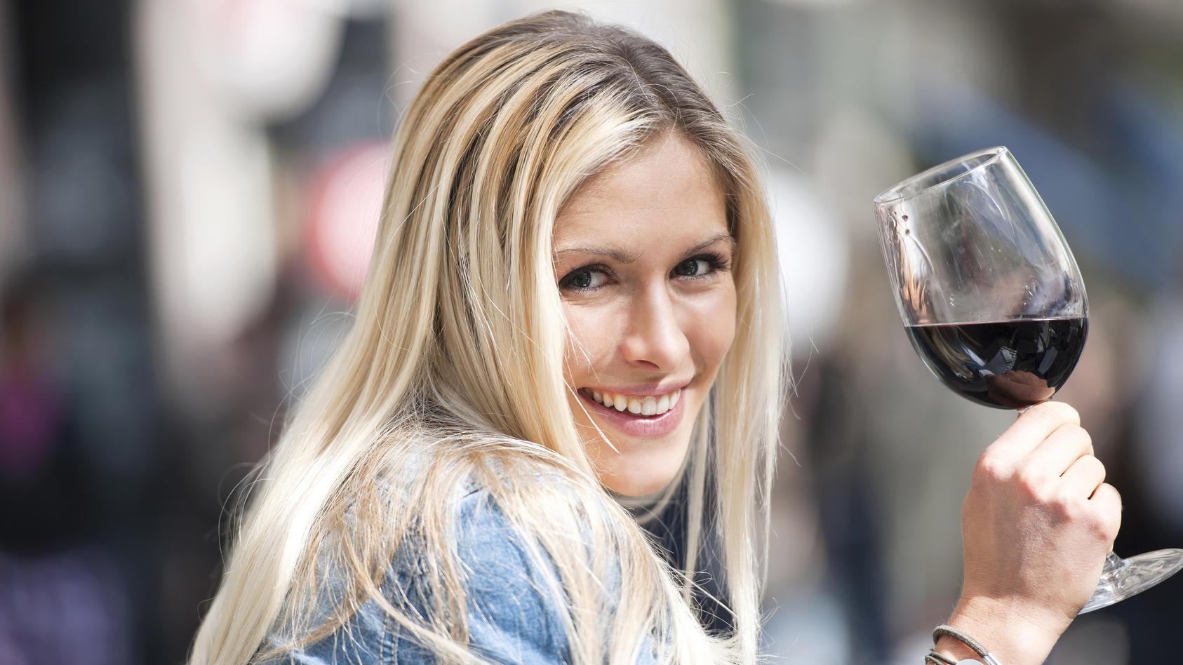 Eine Frau trinkt Rotwein.