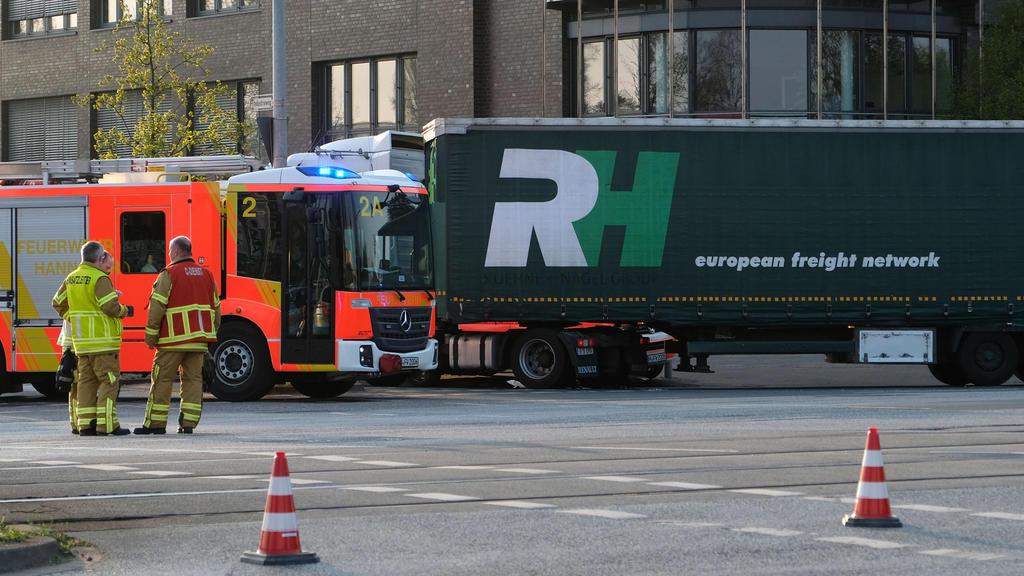 18.04.2018, Niedersachsen, Hannover: Feuerwehrmänner stehen an einer Unfallstelle neben einem Lastwagen. Ein Junge ist am Mittwoch von einem Lastwagen überrollt und getötet worden. Das Kind war offenbar mit einem Fahrrad an einer Kreuzung unterwegs,