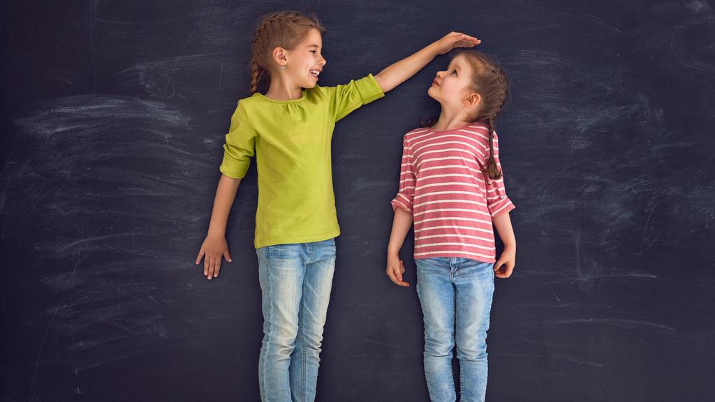 Kinder messen ihre Körpergröße.
