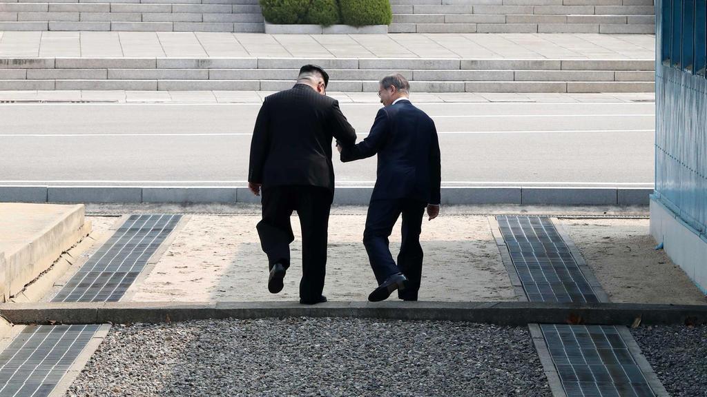 dpatopbilder - 27.04.2018, Südkorea, Panmunjom: Kim Jong Un (l), Machthaber von Nordkorea, und Moon Jae In, Präsident von Südkorea, gehen Hand in Hand über die Betonschwelle, die die Grenze zwischen ihren Ländern markiert nach Nordkorea. Als erster n
