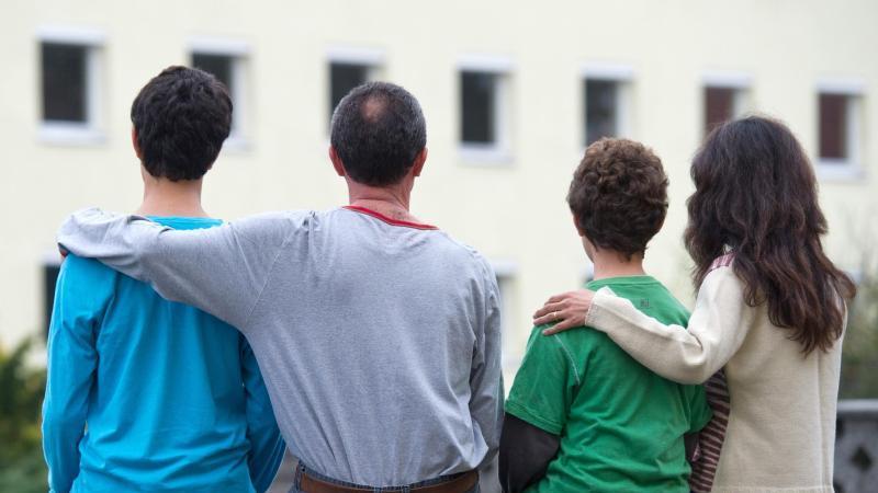 Eine syrische Familie sitzt vor einem Wohnheim der Zentralen Ausländerbehörde des Landes Brandenburg. Foto: Patrick Pleul/Illustration