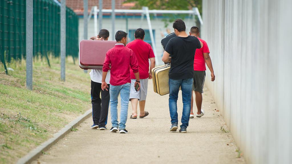 ARCHIV - 27.08.2015, Rheinland-Pfalz, Ingelheim: Flüchtlinge laufen mit Koffern bepackt auf einem Weg einer Erstaufnahmeeinrichtung für Flüchtlinge.   (zu dpa «Ein Band über die Geschichte und Gegenwart der Migration» vom 14.05.2018) Foto: Christoph