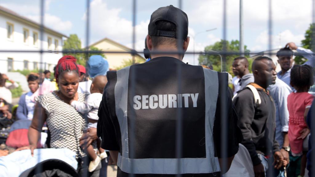 ARCHIV - 15.05.2018, Manching, Bayern: Im Transitzentrum für Asylsuchende steht eine Sicherheitskraft Bewohnern gegenüber. Das Transitzentrum könnte eines von mehreren sogenannten Ankerzentren werden. Diese Zentren sollen die schnelle Abschiebung von