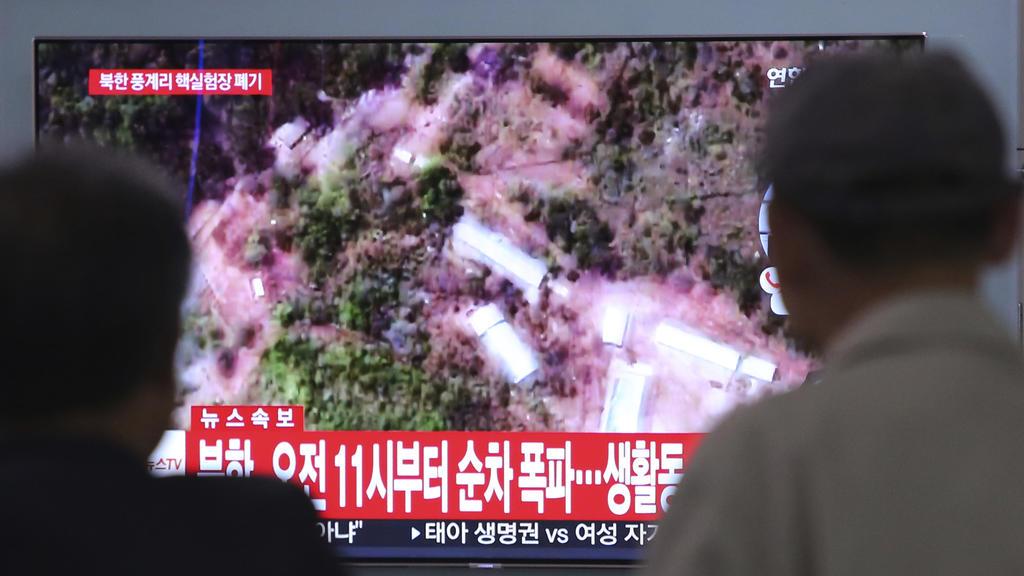 24.05.2018, Südkorea, Seoul: Menschen verfolgen am Bahnhof von Seoul eine Nachrichtensendung auf einem Fernseher, die Satellitenbilder von dem Atomtestgelände Punggye-ri in Nordkorea zeigt. Nordkorea hat nach Medienberichten sein umstrittenes Atomtes