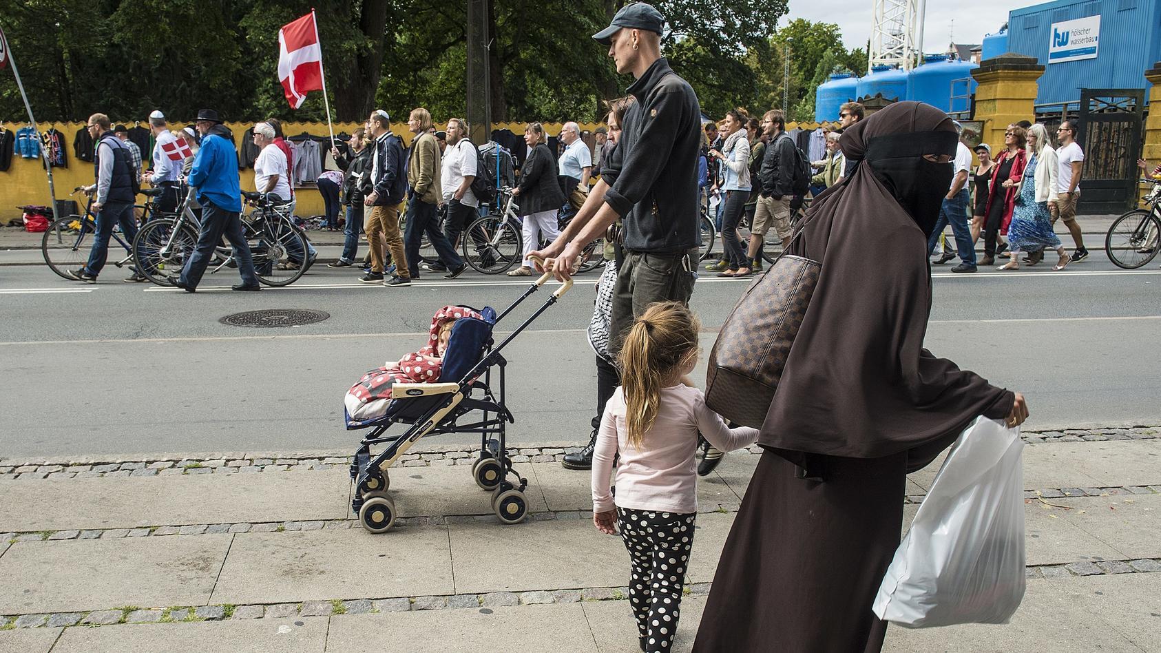 Parallelgesellschaften in Dänemark: Eine Frau in Niqab geht an einer Demonstration vorbei.