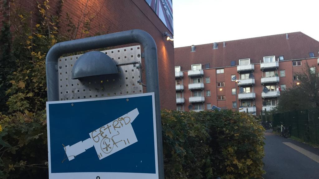Ein Schild weist am 13.11.2017 im Wohnviertel Mjølnerparken in Kopenhagen (Dänemark) auf Videoüberwachung hin. Das Viertel ist seit Monaten Schauplatz von Bandenschießereien. (zu dpa «Straßenkampf im Szeneviertel - Kopenhagen mit Gangs überfordert» v